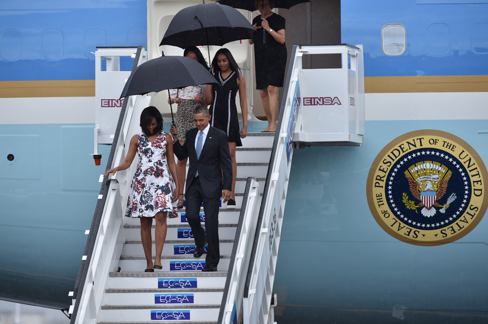 US President Barack Obama (R), First Lady Michelle Obama and daughters Sasha and Malia (behind) arrive at Jose Marti international airport in Havana on March 20, 2016. Obama, who is on a historic three-day visit to the communist-ruled island, flew to Cuba Sunday to bury the hatchet in a more than half-century-long Cold War standoff, but the arrest of dozens of dissidents just as his plane took off underlined the delicacy of the mission. AFP PHOTO/ Yuri CORTEZ / AFP / YURI CORTEZ