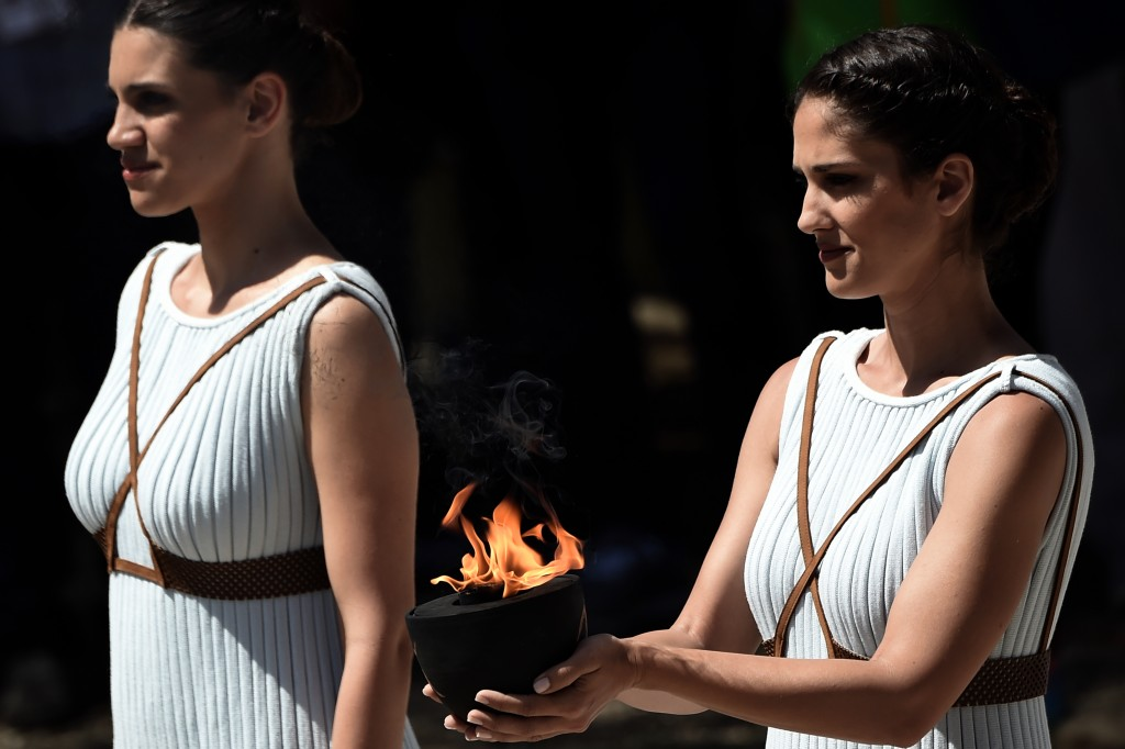 An actress holds a cauldron with the Olympic flame at the Temple of Hera on April 20, 2016 during a dress rehearsal of the lighting ceremony of the Olympic flame in ancient Olympia, the sanctuary where the Olympic Games were born in 776 BC. / AFP PHOTO / ARIS MESSINIS