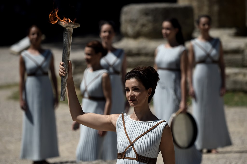 Actress Katerina Lechou acting the high pristess holds a torch with the Olympic flame at the Temple of Hera on April 20, 2016 during a dress rehearsal of the lighting ceremony of the Olympic flame in ancient Olympia, the sanctuary where the Olympic Games were born in 776 BC. / AFP PHOTO / ARIS MESSINIS