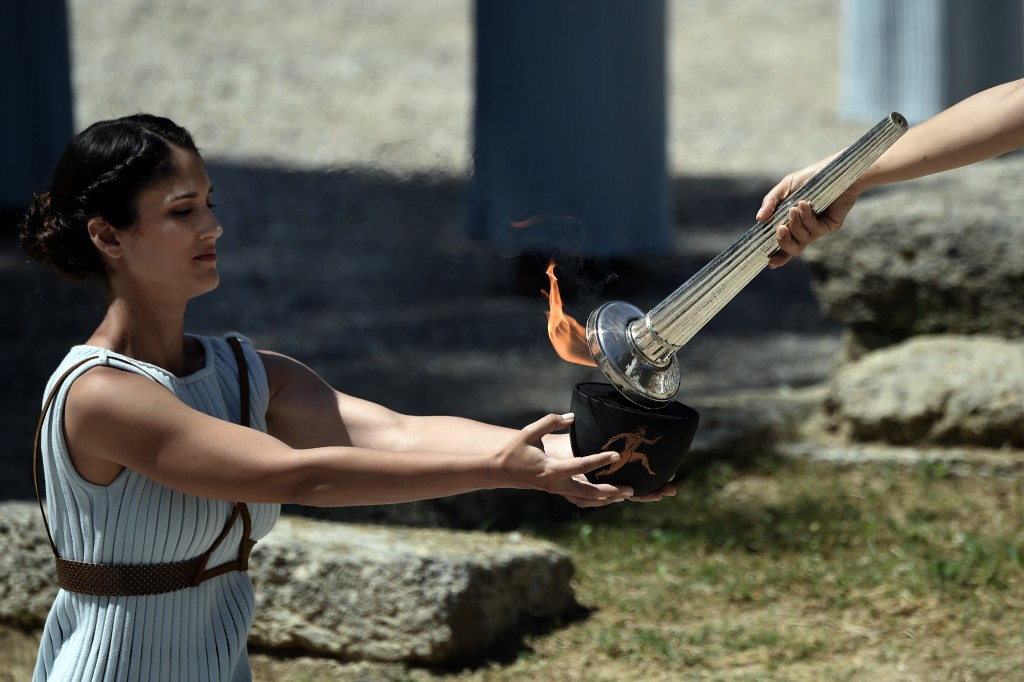 Actress Katerina Lechou (R) acting the high pristess passes the Olympic flame at the Temple of Hera on April 20, 2016 during a dress rehearsal of the lighting ceremony of the Olympic flame in ancient Olympia, the sanctuary where the Olympic Games were born in 776 BC. / AFP PHOTO / ARIS MESSINIS
