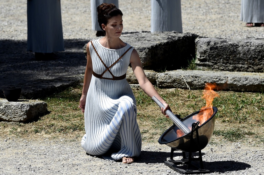 Greek actress Katerina Lechou, acting as the high priestess, lights the Olympic flame at the Temple of Hera in Olympia on April 20, 2016, during a dress rehearsal for the lighting ceremony of the Olympic flame in ancient Olympia, the sanctuary where the Olympic Games were born in 776 BC. / AFP PHOTO / ARIS MESSINIS