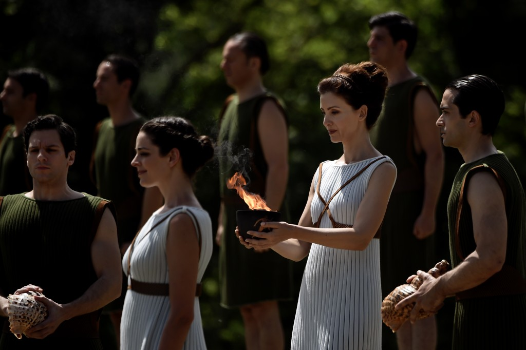 Greek actress Katerina Lechou, acting as the high priestess, holds a cauldron with the Olympic flame at the ancient stadium of Olympia on April 20, 2016, during a dress rehearsal of the lighting ceremony of the Olympic flame in ancient Olympia, the sanctuary where the Olympic Games were born in 776 BC. / AFP PHOTO / ARIS MESSINIS