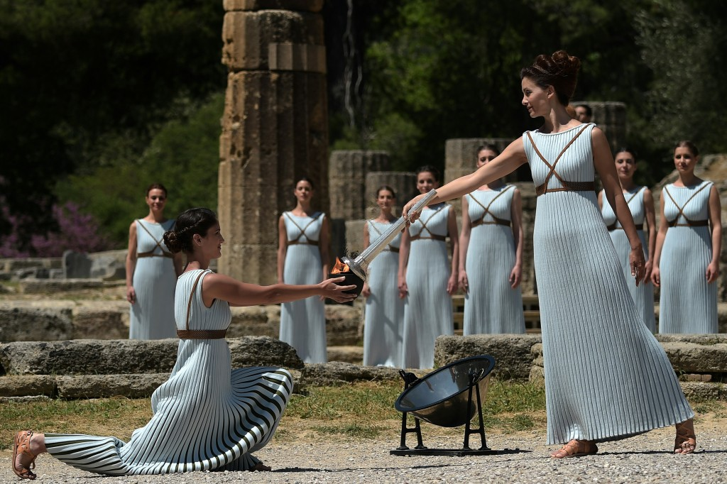 Actress Katerina Lechou (R) acting the high pristess passes the Olympic flame at the Temple of Hera on April 21, 2016 during the lighting ceremony of the Olympic flame in ancient Olympia, the sanctuary where the Olympic Games were born in 776 BC. The Olympic flame was lit Thursday in an ancient temple in one country in crisis and solemnly sent off carrying international hopes that Brazil's political paralysis will not taint the Rio Games that start in barely 100 days. / AFP PHOTO / ARIS MESSINIS