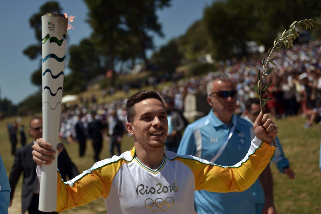 First torchbearer world champion at artistic gymnastics, Lefteris Petrounias runs with the Olympic Flame as he arrives at the Temple of Hera on April 21, 2016 during the lighting ceremony of the Olympic flame in ancient Olympia, the sanctuary where the Olympic Games were born in 776 BC. The Olympic flame was lit Thursday in an ancient temple in one country in crisis and solemnly sent off carrying international hopes that Brazil's political paralysis will not taint the Rio Games that start in barely 100 days. / AFP PHOTO / ARIS MESSINIS
