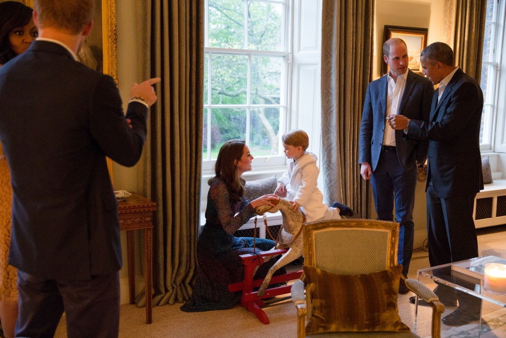 """A handout picture released by Kensington Palace on April 22, 2016 shows Britain's Prince George of Cambridge (R) playing on a rocking horse with his mother Catherine, Duchess of Cambridge, as US President Barack Obama (R) and Prince William, Duke of Cambridge (2R) and US First Lady Michelle Obama (L) and Prince Harry (2L) talk at Kensington Palace in London on April 22, 2016. / AFP PHOTO / KENSINGTON PALACE / WHITE HOUSE PHOTOGRAPHER / PETE SOUZA / RESTRICTED TO EDITORIAL USE, NO COMMERCIAL USE, NO ADVERTISING, NO MERCHANDISING, MANDATORY CREDIT """"AFP / KENSINGTON PALACE / WHITEHOUSE PHOTOGRAPHER / PETE SOUZA"""" RESTRICTED TO SUBSCRIPTION USE - NO SALES - DISTRIBUTED AS A SERVICE TO CLIENTS"""