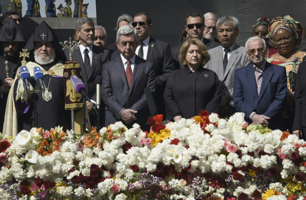 US actor George Clooney (2nd L), Armenian President Serzh Sarkisian (3rd L), his wife Rita Sarkisian and French and Armenian singer Charles Aznavour attend a ceremony at the Genocide Memorial in Yerevan on April 24, 2016, to commemorate the 101st anniversary of the World War I-era Armenian genocide in the Ottoman Empire. A staunch advocate of the massacre's recognition as genocide, Clooney arrived in the ex-Soviet nation on April 23 to take part in the hugely symbolic ceremonies. / AFP PHOTO / KAREN MINASYAN