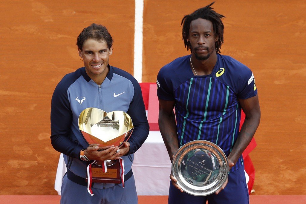 Winner Spain's Rafael Nadal and second placed France's Gael Monfils pose with their trophies during the awarding ceremony following the final tennis match at the Monte-Carlo ATP Masters Series Tournament in Monaco on April 17, 2016. Nadal defeated Monfils 7-5, 5-7, 6-0 to win a record ninth title at the Monte Carlo Masters.  AFP PHOTO / VALERY HACHE / AFP PHOTO / VALERY HACHE