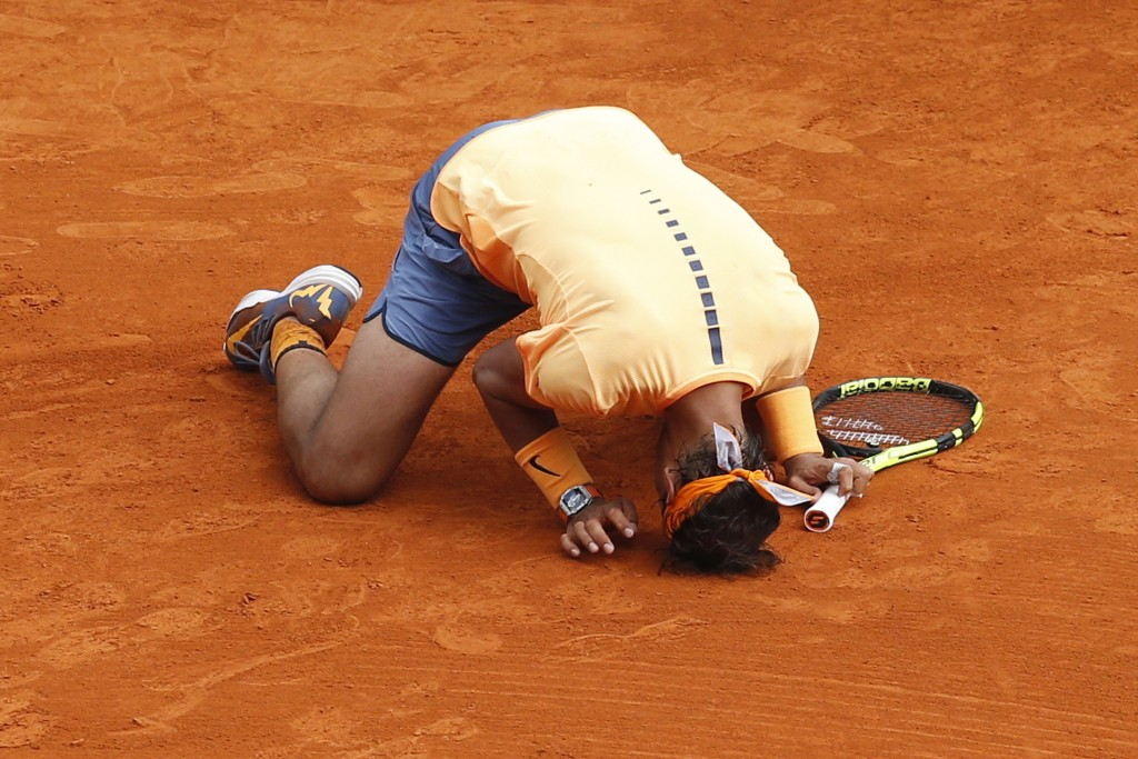 Spain's Rafael Nadal kneels on the court as he celebrates after defeating France's Gael Monfils during the final tennis match at the Monte-Carlo ATP Masters Series Tournament in Monaco on April 17, 2016.   AFP PHOTO / VALERY HACHE / AFP PHOTO / VALERY HACHE