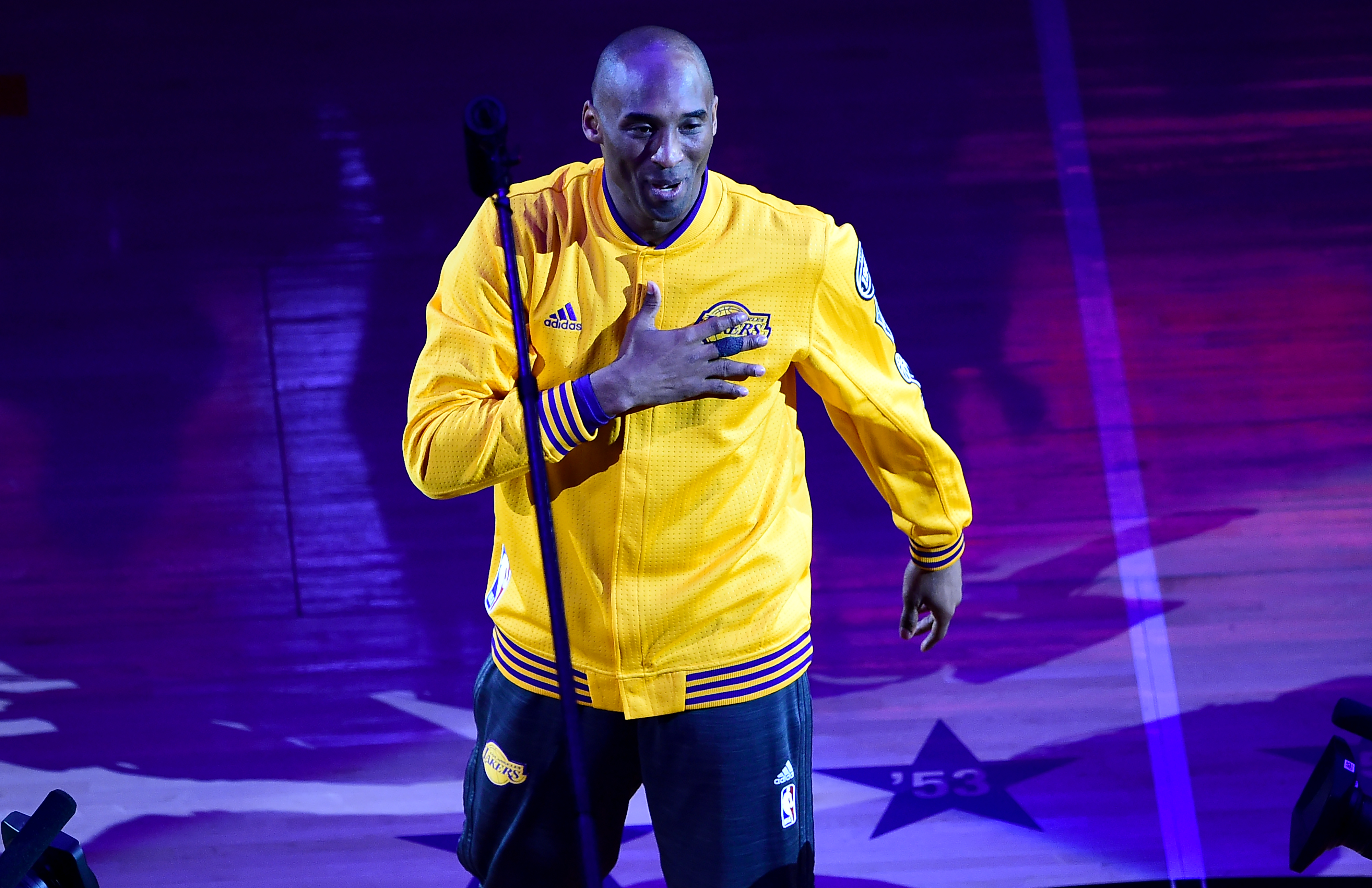 Kobe Bryant gestures as he takes the court for his last game for the Los Angeles Lakers against Utah Jazz in their season-ending NBA western division matchup n Los Angeles, California on April 13, 2016. / AFP PHOTO / FREDERIC J. BROWN