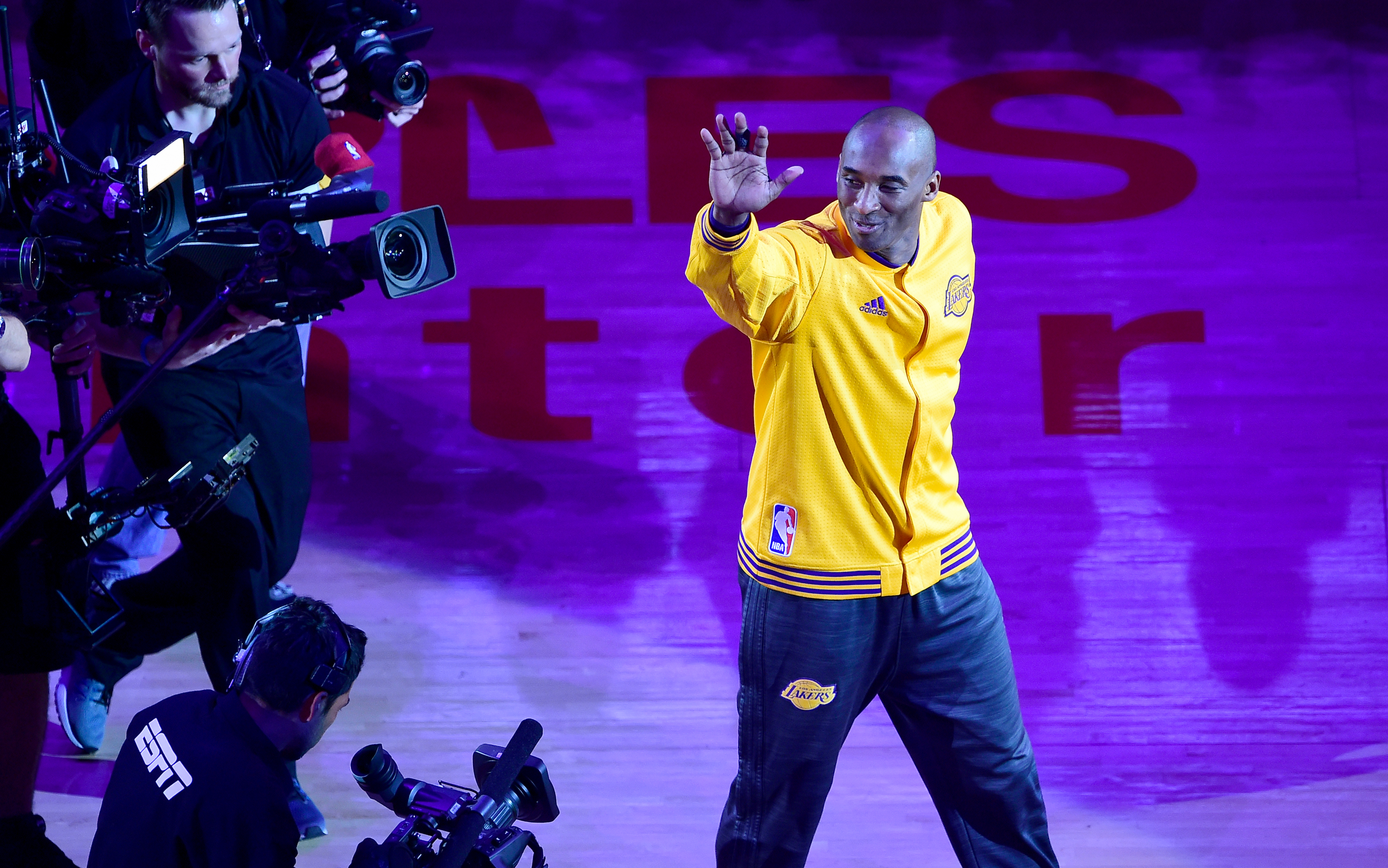 Kobe Bryant gestures to fans as he takes the court for his last game for the Los Angeles Lakers against Utah Jazz in their season-ending NBA western division matchup n Los Angeles, California on April 13, 2016. / AFP PHOTO / FREDERIC J. BROWN