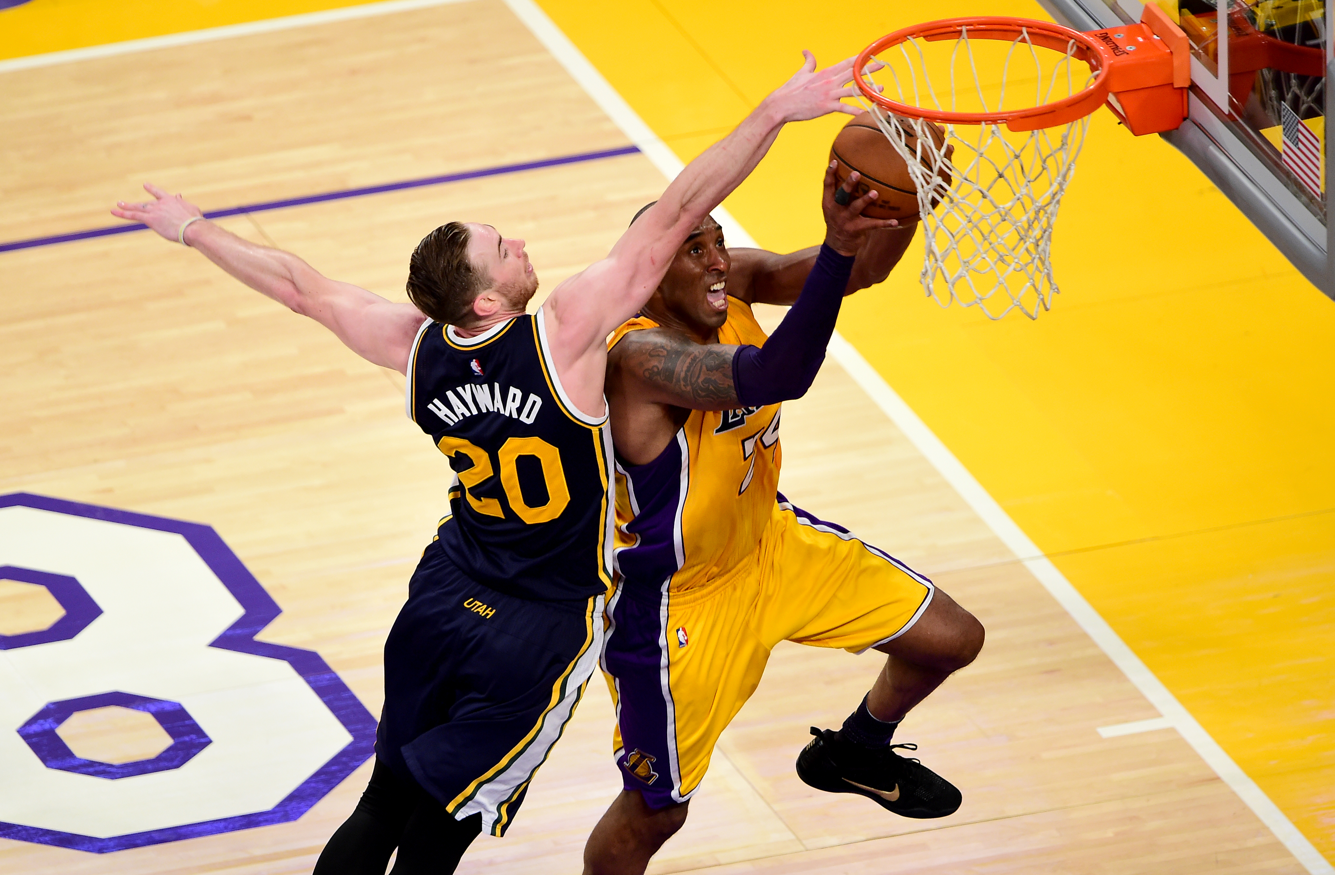 Kobe Bryant (R) of the Los Angeles Lakers goes to the hoop under pressure from Gordon Hayward of the Utah Jazz in Bryant's last game as a Laker during their season-ending NBA western division matchup in Los Angeles, California on April 13, 2016, where the Lakers defeated the Jazz 101-96. / AFP PHOTO / FREDERIC J. BROWN