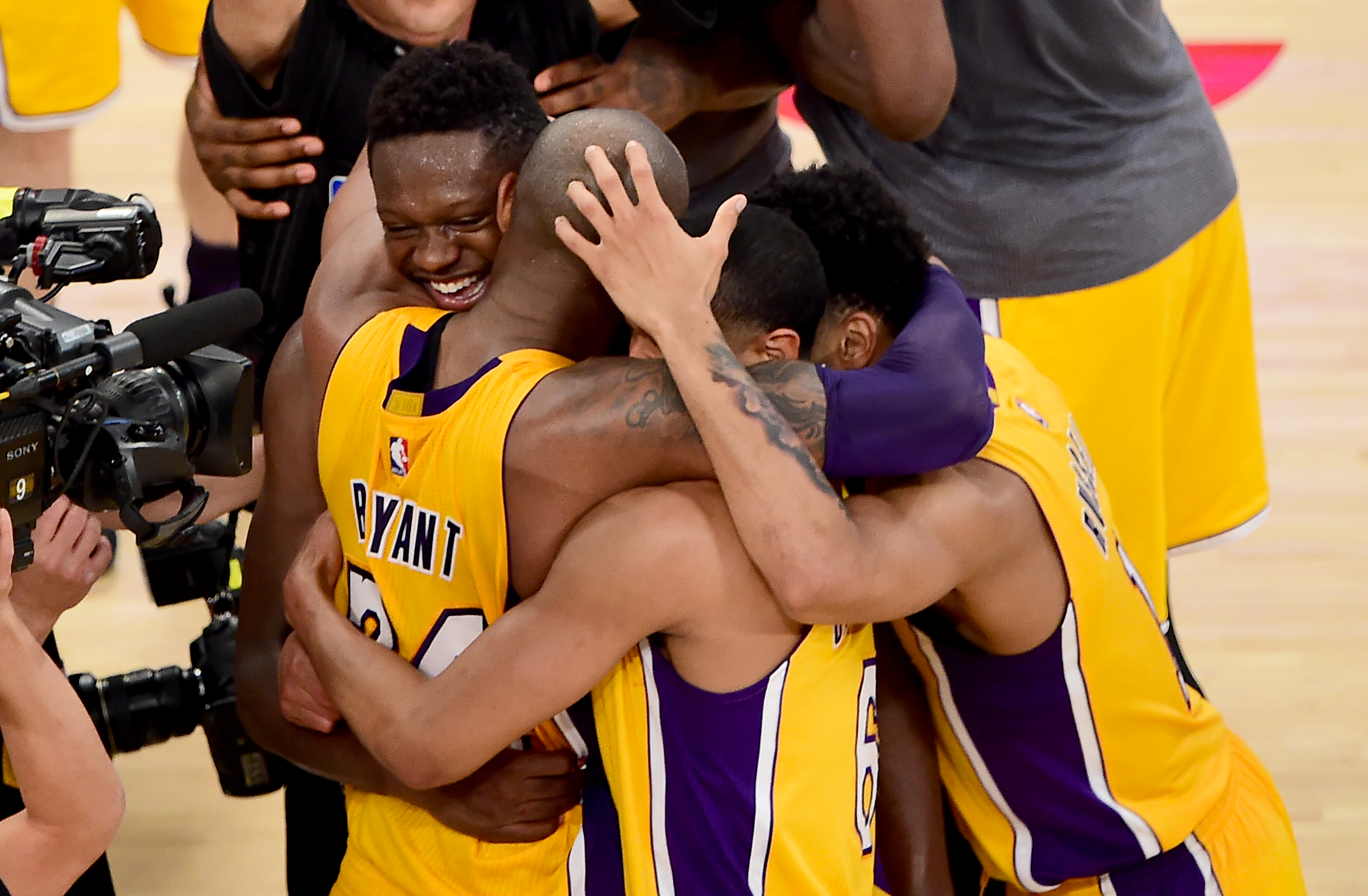 Kobe Bryant of the Los Angeles Lakers celebrates with teammates following his final game as a Laker in their season-ending NBA western division matchup aginst the Utah Jazz in Los Angeles, California on April 13, 2016, where the Lakers defeated the Jazz 101-96. / AFP PHOTO / FREDERIC J. BROWN