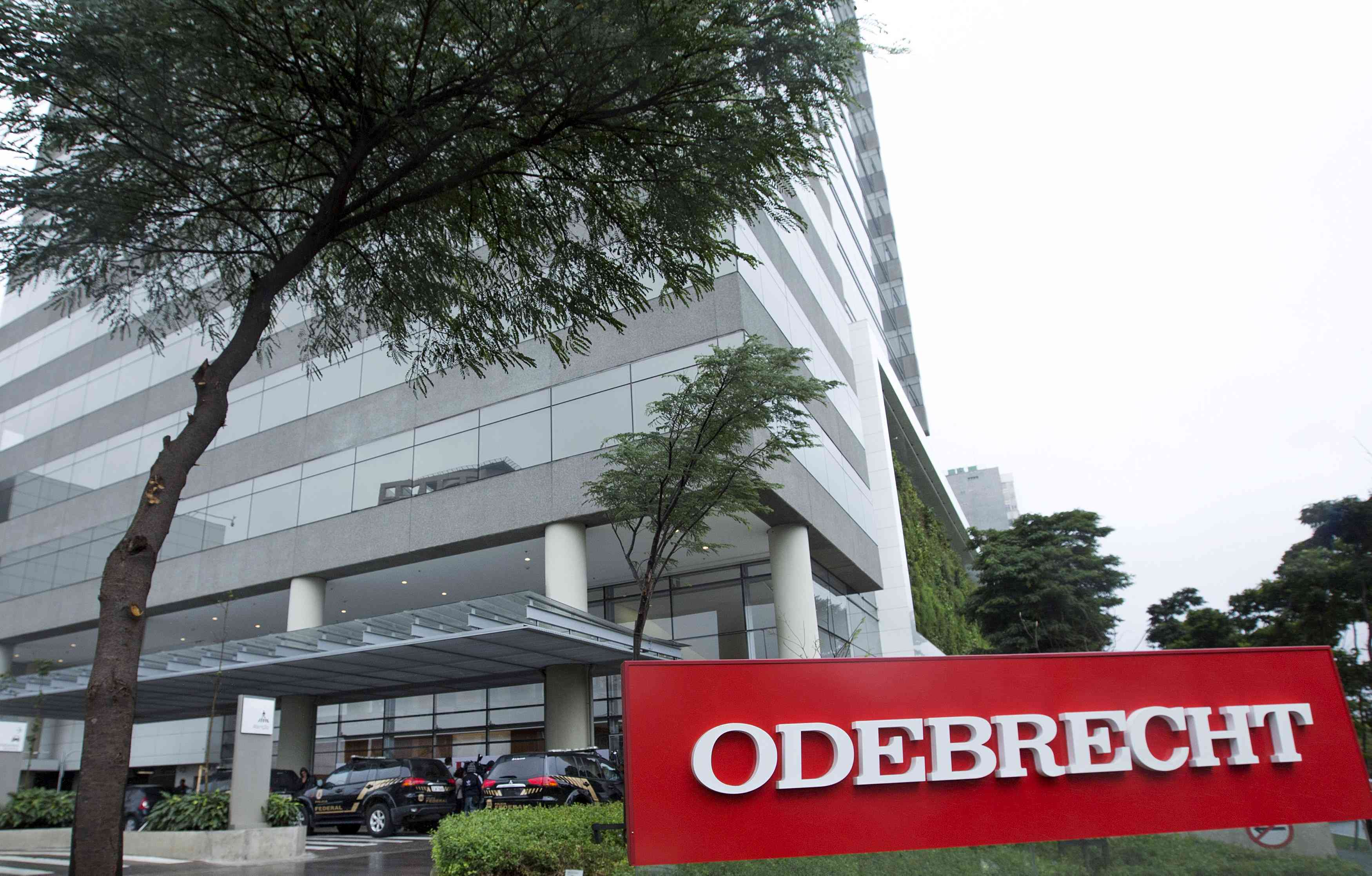 Federal police cars are parked in front of the headquarters of Odebrecht, a large private Brazilian construction firm, in Sao Paulo, Brazil, June 19, 2015. Federal police agent Igor Romario confirmed that Odebrecht CEO Marcelo Odebrecht and Andrade Gutierrez CEO Otavio Marques Azevedo were among 12 people arrested on Friday in a corruption investigation at state-run oil firm Petrobras. Brazilian prosecutor Carlos Fernando dos Santos Lima said at a news conference in the southern city of Curitiba that an investigation into Brazil's two largest construction firms uncovered a sophisticated scheme of illegal acts, including participating in a cartel and fraud in project bidding. REUTERS/Rodrigo Paiva