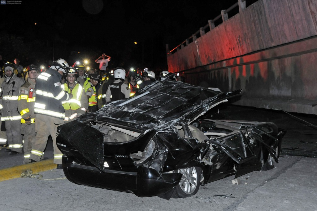 Rescue workers stand before a destroyed car after the collapse of a bridge in an earthquake, April 16, 2016 in Guayaquil, Ecuador.  At least 28 people were killed by a strong 7.8-magnitude earthquake that struck northwestern Ecuador, the country's Vice President Jorge Glas said. A tate of emergency had been declared nationwide.  / AFP PHOTO / MARCOS PIN MENDEZ