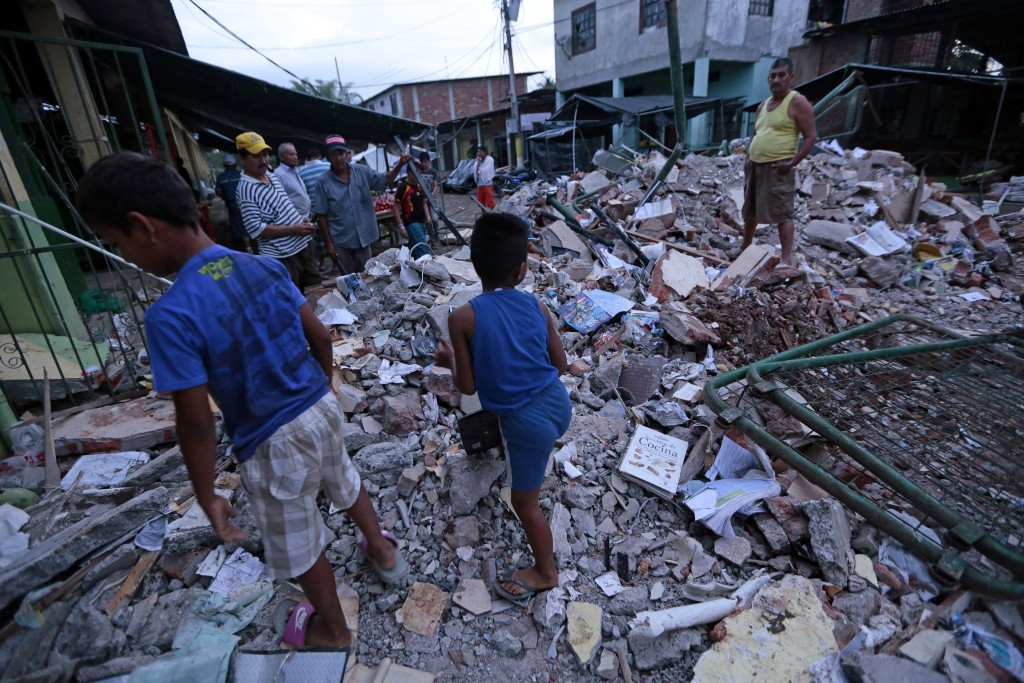People stand amongst the rubble of fallen homes in Manta on April 17, 2016, after a powerful 7.8-magnitude earthquake struck Ecuador on April 16.  At least 77 people were killed when a powerful 7.8-magnitude earthquake struck Ecuador, destroying buildings and a bridge and sending terrified residents scrambling from their homes, authorities in the Latin American country said on April 17. / AFP PHOTO / JUAN CEVALLOS