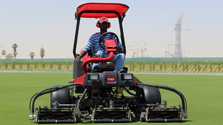 A worker mows grass being grown at a research and development centre to find the best playing surface for the football World Cup in six years time in Doha on April 26, 2016.  Watching grass grow is not usually considered exciting but there's currently a buzz of anticipation among Qatar's World Cup organisers about 12 different types of turf gently sprouting on former Doha farmland. If all goes well, one of these dozen grasses will eventually take centre stage and become the most watched strips of green on the globe, at least for a 28-day period, during the 2022 World Cup.   / AFP PHOTO / KARIM JAAFAR / TO GO WITH AFP STORY BY DAVID HARDING
