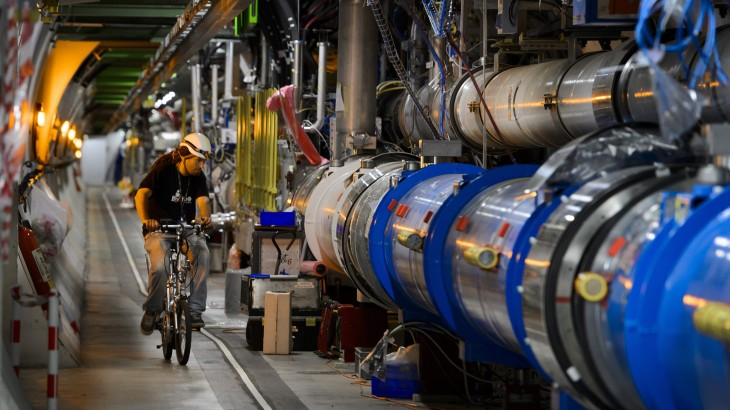 """(FILES) This file photo taken on July 19, 2013 shows a worker riding his bicycle in a tunnel of the European Organisation for Nuclear Research (CERN) Large Hadron Collider (LHC), during maintenance works in Meyrin, near Geneva.  A weasel shut down the world's most powerful particle smasher when it wandered onto a 66,000-volt transformer and caused a short circuit, Europe's physics lab CERN said on April 30, 2016. The Large Hadron Collider (LHC) was halted """"following technical issues, including a power cut due to the passage of a weasel on a high voltage electrical transformer,"""" CERN spokesman Arnaud Marsollier told AFP. / AFP PHOTO / FABRICE COFFRINI"""