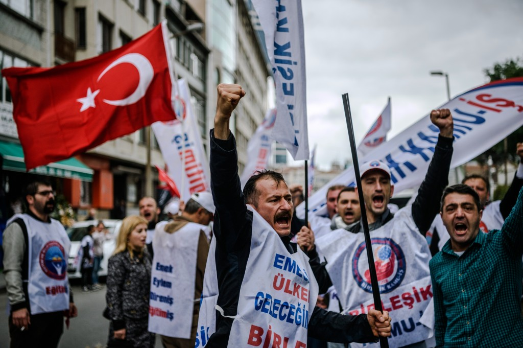 Demonstrators shout slogans and hold up their fists during a May Day rally in Sisli, a district of Istanbul, on May 1, 2016.  Turkish labour activists and leftists marked the annual May Day holiday, with thousands of security deployed and bracing for trouble after the authorities refused to allow protests in central Taksim Square. / AFP PHOTO / OZAN KOSE