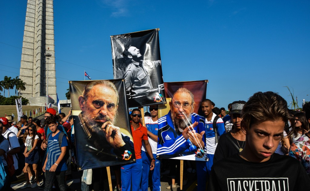 People display images of Cuban former president Fidel Castro during the May Day parade at Revolution Square in Havana, on May 1, 2016. / AFP PHOTO / JORGE BELTRAN