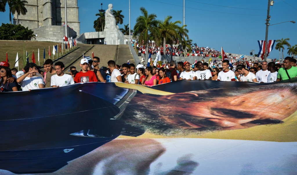 People display an image of Cuban former president Fidel Castro during the May Day parade at Revolution Square in Havana, on May 1, 2016. / AFP PHOTO / JORGE BELTRAN