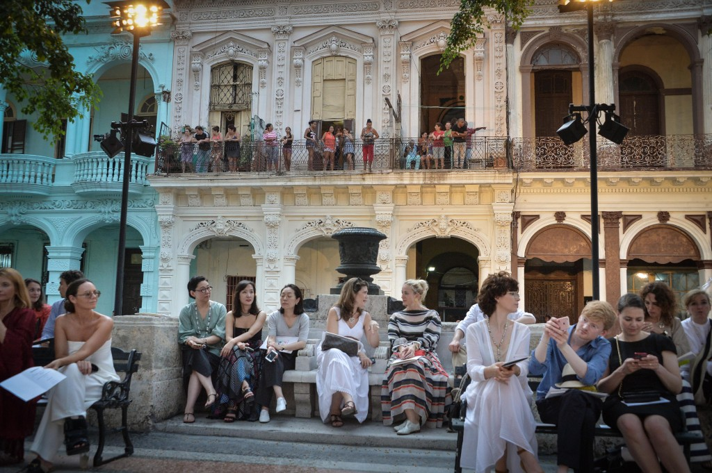 From their houses (at back) Cubans try to watch the Chanel performance at the Prado promenade in Havana, on May 3, 2016. / AFP PHOTO / ADALBERTO ROQUE