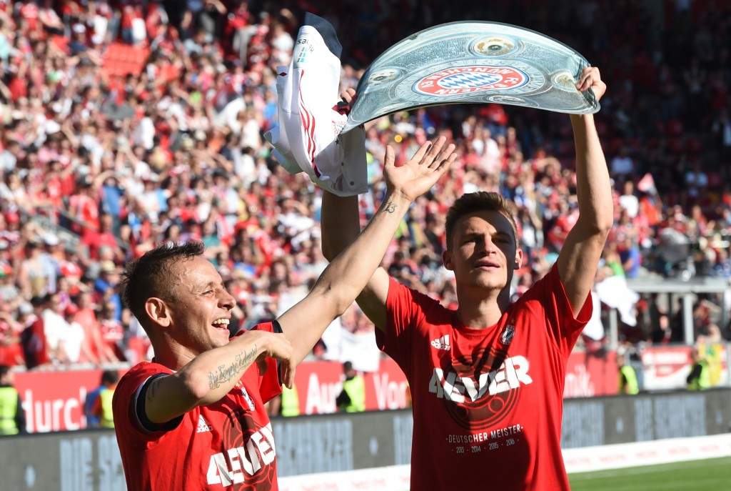 Bayern Munich's Brazilian defender Rafinha (L) and Bayern Munich's midfielder Joshua Kimmich (R) celebrate with a paper mock up of the Bundesliga trophy after the German first division Bundesliga football match between FC Ingolstadt 04 and FC Bayern Munich, at the Audi Sportpark in Ingolstadt, southern Germany, on May 7, 2016. / AFP PHOTO / CHRISTOF STACHE / RESTRICTIONS: DURING MATCH TIME: DFL RULES TO LIMIT THE ONLINE USAGE TO 15 PICTURES PER MATCH AND FORBID IMAGE SEQUENCES TO SIMULATE VIDEO. == RESTRICTED TO EDITORIAL USE == FOR FURTHER QUERIES PLEASE CONTACT DFL DIRECTLY AT + 49 69 650050