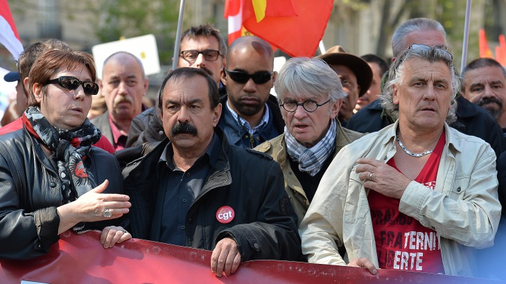 (L-R) Leaders of French worker's unions Bernadette Groison of the Federation Syndicale Unitaire (FSU), Philippe Martinez of the General Confederation of Labour (CGT) and Jean-Claude Mailly of Force Ouvriere (FO) hold a banner at the head of a march during a traditional May Day demonstration on May 1, 2016, in Paris. AFP PHOTO / MIGUEL MEDINA / AFP PHOTO / MIGUEL MEDINA