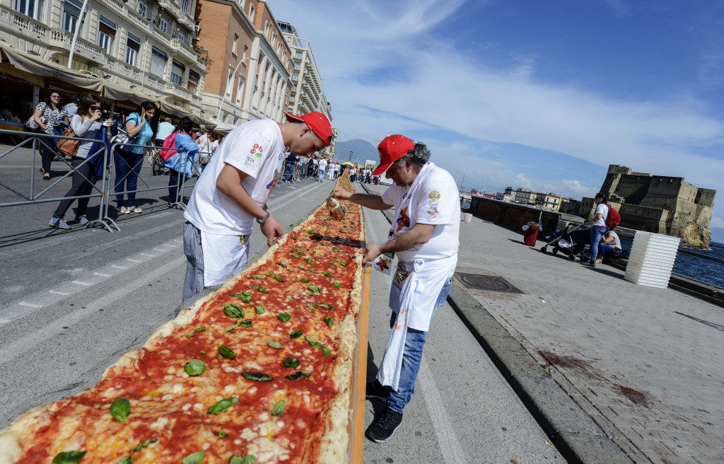 Neapolitan pizza makers attempt to make the longest pizza to break a Guinness World Record along the seafront of Naples, on May 18, 2016. For the wood-fired pizza, which measured two kilometres, they used 2,000 kg of flour, 1,600 kg of tomatoes, 2,000 kg of mozzarella, 200 litres of oil, 30kg of fresh basil. The record-breaking snack measured up at exactly 1,853.88 metres (6,082 feet), smashing the previous record of 1,595.45 metres (5,234 feet) set at last year's World Expo in Milan, Italy's food and agriculture board Coldiretti said. / AFP PHOTO / Mario LAPORTA