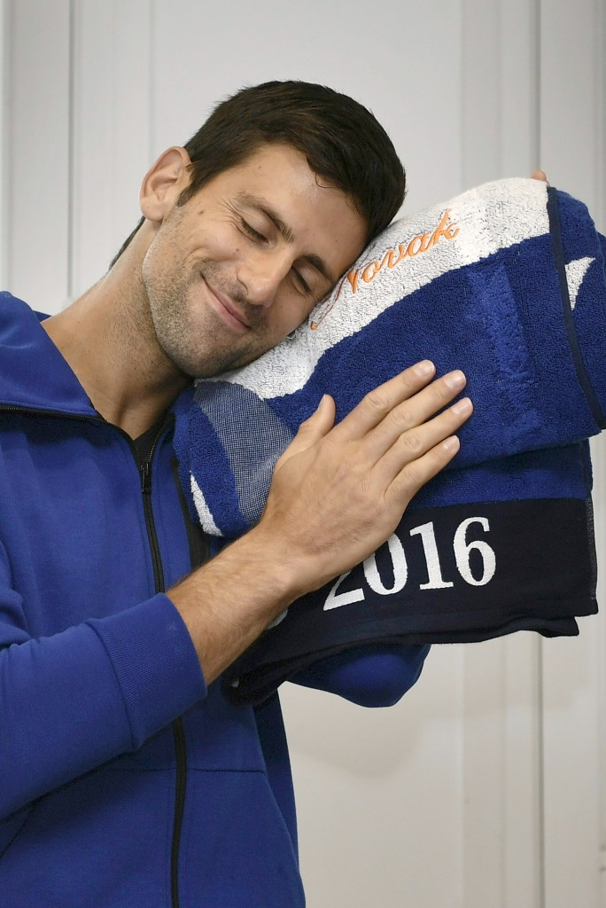 Serbia's Novak Djokovic smiles with a towel embroidered with his name after cutting his birthday cake at the Roland Garros 2016 French Tennis Open in Paris on May 22, 2016. / AFP PHOTO / Philippe LOPEZ