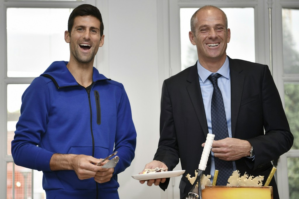 Serbia's Novak Djokovic (L) smiles next to Roland Garros Director Guy Forget as he cuts his birthday cake at the Roland Garros 2016 French Tennis Open in Paris on May 22, 2016. / AFP PHOTO / Philippe LOPEZ