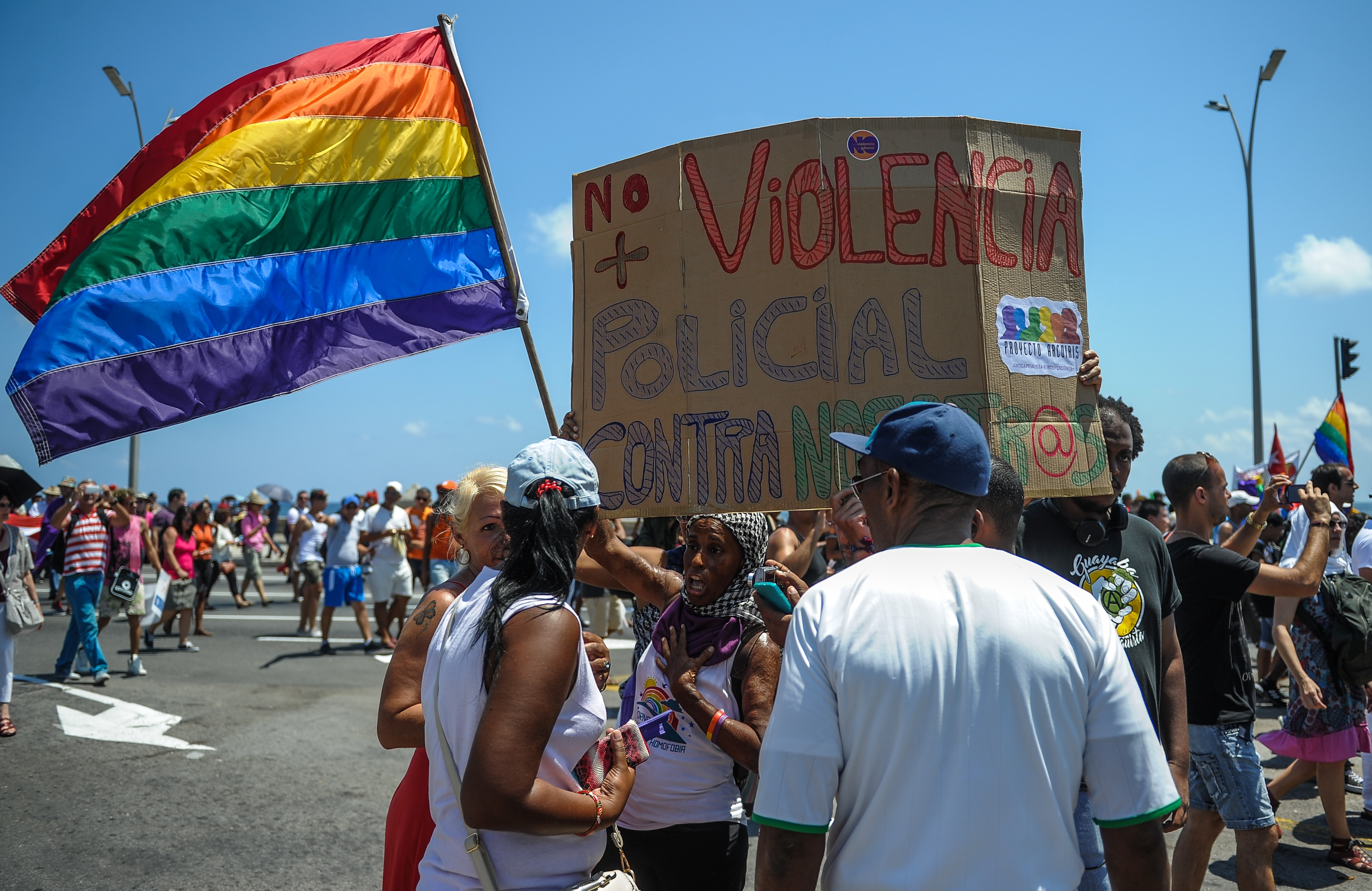 "Members of the gay and lesbian community hold a sign reading ""No more police violence against us"" during a march against homophobia on May 14, 2016 in Havana. / AFP PHOTO / YAMIL LAGE"
