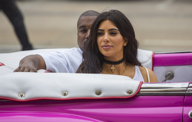 American reality-show star Kim Kardashian West and her husband, rap superstar, Kayne West ride on a classic car in Havana, Cuba, Wednesday, May 4, 2016. West, Kardashian and members of her reality-show-star family have become the latest celebrities to visit Havana. They visited Havana's Museum of Rum Wednesday, stepping out of a hot-pink antique American convertible as they snapped selfies and were recorded by a television crew following them around.(AP Photo/Desmond Boylan)