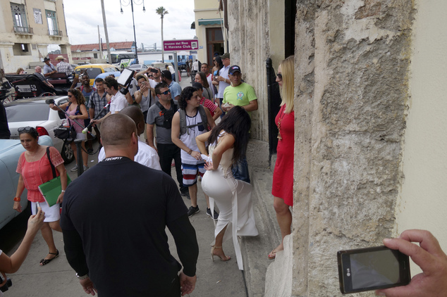 American reality-show star Kim Kardashian West, center in white, enters the Havana Club Rum Museum in Havana, Cuba, Wednesday, May 4, 2016. Rap superstar Kayne West, his wife Kim Kardashian and members of her reality-show-star family have become the latest celebrities to visit Havana. They visited Havana's Museum of Rum Wednesday, stepping out of a hot-pink antique American convertible as they snapped selfies and were recorded by a television crew following them around.(AP Photo/Desmond Boylan)