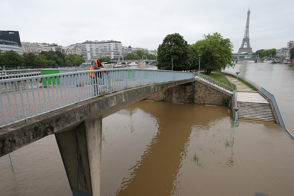A municipal employee works on a bridge in Paris on June 3, 2016, after the banks of the River Seine became flooded following heavy rainfalls. The rain-swollen river Seine in Paris reached its highest level in three decades, spilling its banks and prompting the Louvre museum to shut its doors and evacuate artworks in its basement. Parisians were urged to avoid the banks of the river which was expected to reach a peak of six metres (19 feet), while deadly floods continued to wreak havoc elsewhere in France and Germany.  / AFP PHOTO / JOEL SAGET
