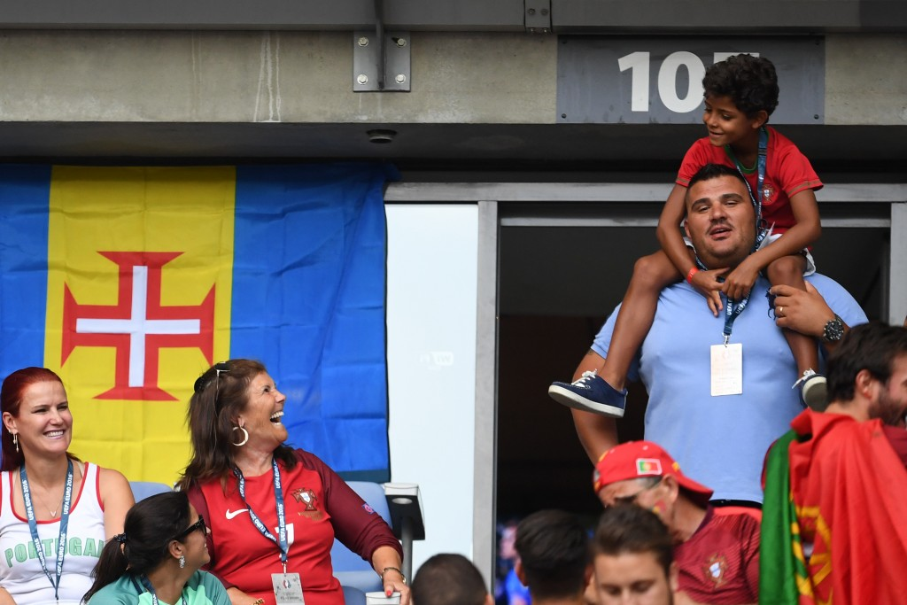 Portugal's forward Cristiano Ronaldo's mother Maria Dolores dos Santos Aveiro (C) looks at her grandchild Cristiano Junior (top) next to her daughter Elma Aveiro (L) as they cheer ahead of the Euro 2016 final football match between Portugal and France at the Stade de France in Saint-Denis, north of Paris, on July 10, 2016. / AFP PHOTO / FRANCISCO LEONG