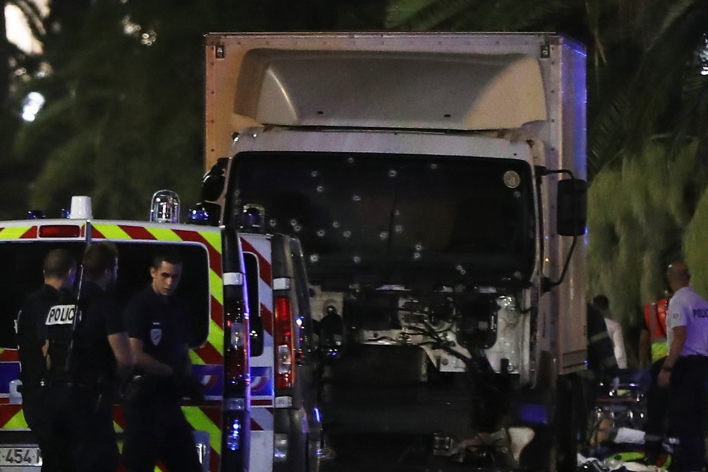 """Police officers stand near a van, with its windscreen riddled with bullets, that ploughed into a crowd leaving a fireworks display in the French Riviera town of Nice on July 14, 2016. Up to 30 people are feared dead and over 100 others were injured after a van drove into a crowd watching Bastille Day fireworks in the French resort of Nice on July 14, a local official told French television, describing it as a """"major criminal attack"""". / AFP PHOTO / VALERY HACHE"""