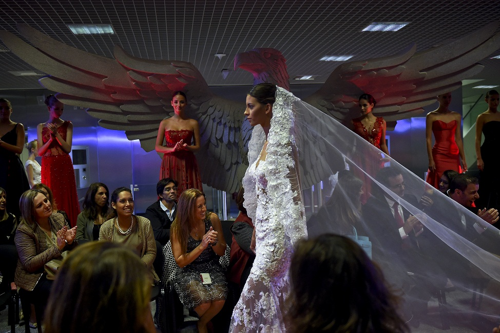Models wear creations by designer Micaela Oliveira during a presentation by Portuguese football club Benfica of 24 wedding dresses, 12 evening dresses and four dresses for girls at the Stadium of Light in Lisbon. Heavily indebted Portuguese giants Benfica unveiled tonight its first-ever collection of wedding dresses which it will sell alongside other club items such as jerseys, baby diapers and dog beds. / AFP PHOTO / PATRICIA DE MELO MOREIRA