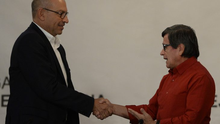 """Colombia's National Liberation Army (ELN) left-wing guerrilla delegate Pablo Beltran (R) shakes hand with the head of the delegation of the Colombian government, Mauricio Rodriguez (L), at the Foreign Ministry in Caracas, on October 10, 2016. """"The government and ELN delegations have decided to launch talks on October 27 in Quito,"""" according to the joint statement. / AFP PHOTO / FEDERICO PARRA"""