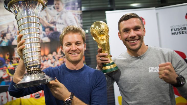 Formula One World Champion Nico Rosberg (L) raises the trophy next to former German player Lukas Podolski with the football World Cup trophy at the airport in Cologne, western Germany on December 7, 2016. / AFP PHOTO / dpa / Rolf Vennenbernd / Germany OUT
